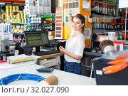 Купить «Young female seller standing at the counter in household tools store», фото № 32027090, снято 17 мая 2018 г. (c) Яков Филимонов / Фотобанк Лори
