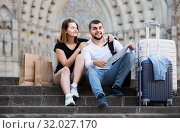 Smiling man and woman sitting at stairs with map. Стоковое фото, фотограф Яков Филимонов / Фотобанк Лори