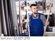 Купить «worker choosing plastic edging for tiles and flooring in workshop», фото № 32027270, снято 15 марта 2017 г. (c) Яков Филимонов / Фотобанк Лори