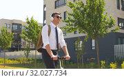 Купить «businessman with headphones riding scooter in city», видеоролик № 32027734, снято 5 августа 2019 г. (c) Syda Productions / Фотобанк Лори
