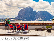 Italy. Dolomiti 19.06.2019: European people take selfies and admire the dolomites mountains scenery Sassolungo or Longkofel. View opens from the hotel restaurant located on top of funicular Col Raiser. Редакционное фото, фотограф Алексей Ширманов / Фотобанк Лори