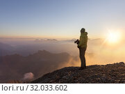 A photographer admires the sunrise at Punta Penia, Marmolada group, Dolomites, Canazei, Trento province, Trentino-Alto Adige, Italy. Редакционное фото, фотограф Clickalps SRLs / age Fotostock / Фотобанк Лори