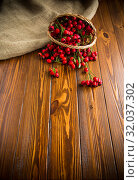 ripe red dogrose in a basket on a wooden. Стоковое фото, фотограф Peredniankina / Фотобанк Лори