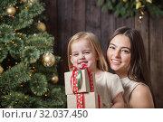Купить «mother and daughter at the Christmas tree on a wooden background», фото № 32037450, снято 16 декабря 2018 г. (c) Майя Крученкова / Фотобанк Лори