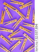 Купить «Background and frame of wooden yellow clothespins on lilac-purple background. View from above. Copy space. The concept of naturalness and eco», фото № 32037894, снято 19 июня 2019 г. (c) Tetiana Chugunova / Фотобанк Лори