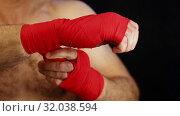 Close up man boxer wrapping wrists with red wrap. Стоковое видео, видеограф Anton Eine / Фотобанк Лори