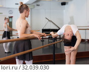 Купить «Choreographer helping young man dancer to have right position. Exercising at the barre by the mirror», фото № 32039030, снято 26 апреля 2019 г. (c) Яков Филимонов / Фотобанк Лори