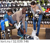 Купить «Young woman helping her husband and son choose new ski boots», фото № 32039146, снято 16 апреля 2019 г. (c) Яков Филимонов / Фотобанк Лори