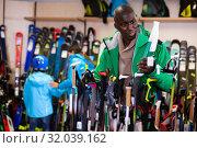 Young African American skier choosing ski poles in sport goods store. Стоковое фото, фотограф Яков Филимонов / Фотобанк Лори