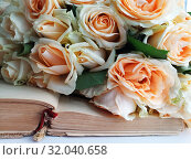 A bouquet of roses lies on an old open book. Стоковое фото, фотограф vlasova / Фотобанк Лори