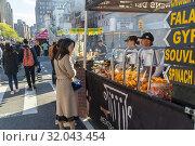 Foodies choose Mediterranean cuisine at a street fair in the Chelsea neighborhood of New York on a warm Saturday, April 27, 2019. (© Richard B. Levine). Редакционное фото, фотограф Richard Levine / age Fotostock / Фотобанк Лори