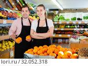 Купить «Young male and woman standing and holding fresh oranges in fruit store», фото № 32052318, снято 27 апреля 2019 г. (c) Яков Филимонов / Фотобанк Лори