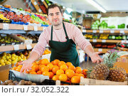 Young man in apron selling fresh oranges and fruits on the supermarket. Стоковое фото, фотограф Яков Филимонов / Фотобанк Лори