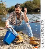 Купить «Upset fisherman displeased with fish catch», фото № 32052370, снято 15 марта 2019 г. (c) Яков Филимонов / Фотобанк Лори