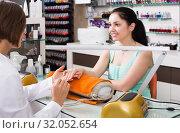 Купить «polite female manicurist filing and shaping nails in beauty salon», фото № 32052654, снято 28 апреля 2017 г. (c) Яков Филимонов / Фотобанк Лори