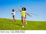 Купить «Happy girls run with ribbons on the field», фото № 32058502, снято 15 июня 2019 г. (c) Сергей Новиков / Фотобанк Лори