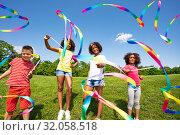 Купить «Children wave colorful ribbons in park together», фото № 32058518, снято 15 июня 2019 г. (c) Сергей Новиков / Фотобанк Лори