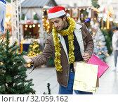 Купить «Young positive man buying Christmas tree and toys at Christmas Fair», фото № 32059162, снято 4 декабря 2018 г. (c) Яков Филимонов / Фотобанк Лори