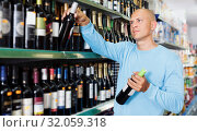Купить «Male consumer buying bottle of red wine in winery store», фото № 32059318, снято 4 июля 2018 г. (c) Яков Филимонов / Фотобанк Лори