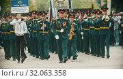RUSSIA, KAZAN 09-08-2019: A wind instrument parade - military musicians in green costumes marching on the street holding musical instruments - a man holding a nameplate says Rostov-on-Don Orchestra. Редакционное видео, видеограф Константин Шишкин / Фотобанк Лори