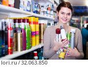 Купить «positive woman customer deciding on hair care products in shop», фото № 32063850, снято 21 февраля 2017 г. (c) Яков Филимонов / Фотобанк Лори
