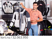 Купить «Male customer is demonstrating modern jacket that he choose», фото № 32063950, снято 1 сентября 2017 г. (c) Яков Филимонов / Фотобанк Лори