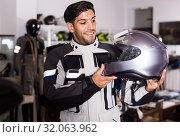 Купить «Man in moto jacket is choosing new helmet for motorbike in the store.», фото № 32063962, снято 1 сентября 2017 г. (c) Яков Филимонов / Фотобанк Лори