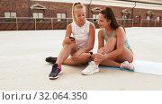 Купить «sporty women or friends with smartphone on rooftop», видеоролик № 32064350, снято 4 августа 2019 г. (c) Syda Productions / Фотобанк Лори