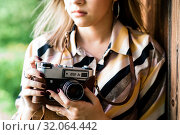 Девушка держит в руках старый плёночный фотоаппарат (2019 год). Редакционное фото, фотограф Игорь Низов / Фотобанк Лори