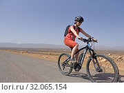 Young woman mountain biking with electric assistance on a straight road through the reg, from Agdz to Zagora, Draa River valley, Province of Zagora, Region Draa-Tafilalet, Morocco, North West Africa. (2019 год). Редакционное фото, фотограф Christian Goupi / age Fotostock / Фотобанк Лори