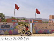 Mountain biker with electric assistance passing by the entrance of a school on the edge of a track through the reg, from Agdz to Zagora, Draa River valley... (2019 год). Редакционное фото, фотограф Christian Goupi / age Fotostock / Фотобанк Лори