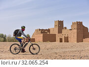 Купить «Mountain biker with electric assistance passing by a ruined ksar on the edge of a track through the reg, between Agdz and Zagora, Draa River valley, Province...», фото № 32065254, снято 25 марта 2019 г. (c) age Fotostock / Фотобанк Лори