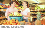 Positive family couple standing with full cart after shopping and pointing to shelves in fruit store. Стоковое видео, видеограф Яков Филимонов / Фотобанк Лори