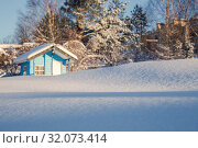 Купить «Winter landscape. Drifts of snow sparkling in the sun against a blurred background of a small house and trees covered with snow. Shallow depth of field», фото № 32073414, снято 6 марта 2019 г. (c) Юлия Бабкина / Фотобанк Лори