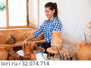 Купить «Female artisan in ceramics workshop with pottery wheel and various clay vessels», фото № 32074714, снято 19 ноября 2019 г. (c) Яков Филимонов / Фотобанк Лори