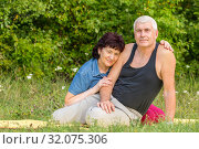 Купить «Mature beautiful couple in love on a green lawn in a park on a summer sunny day.», фото № 32075306, снято 9 августа 2019 г. (c) Акиньшин Владимир / Фотобанк Лори