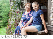 Preteen girl a granddaughter sitting on stairs with her grandma, timber house in forest, copy space. Стоковое фото, фотограф Кекяляйнен Андрей / Фотобанк Лори