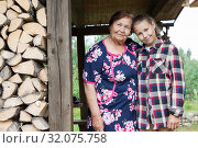 Portrait of elderly grandmother with her granddaughter, standing under roof of timber house near stack of woodpiles. Стоковое фото, фотограф Кекяляйнен Андрей / Фотобанк Лори