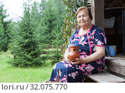 Senior woman holding crock in hands while sitting on wooden stair of veranda, timber house in countryside, copyspace. Стоковое фото, фотограф Кекяляйнен Андрей / Фотобанк Лори