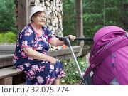 Elderly woman shakes a baby pram, sitting on porch of country house. Great-grandmother with infant. Стоковое фото, фотограф Кекяляйнен Андрей / Фотобанк Лори