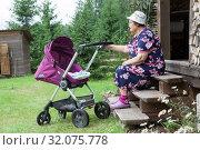 Купить «Senior woman sitting on timber house porch with baby carriage, caring great-grandchild on backyard», фото № 32075778, снято 20 июля 2019 г. (c) Кекяляйнен Андрей / Фотобанк Лори