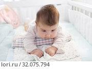 Двухмесячный малыш пытается держать головку, лежа на валике из полотенца. Стоковое фото, фотограф Кекяляйнен Андрей / Фотобанк Лори