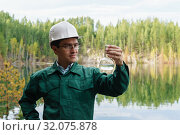 Купить «Industrial ecologist visually evaluates the response of a water sample from lake at the site of a flooded mining pit», фото № 32075878, снято 10 августа 2019 г. (c) Евгений Харитонов / Фотобанк Лори