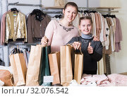 Delighted woman with daughter in clothing store. Стоковое фото, фотограф Яков Филимонов / Фотобанк Лори