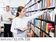 Купить «girl searching for textbooks on bookshelves», фото № 32076726, снято 22 февраля 2018 г. (c) Яков Филимонов / Фотобанк Лори