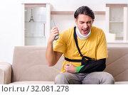 Купить «Young man after car accident suffering at home», фото № 32081278, снято 21 февраля 2019 г. (c) Elnur / Фотобанк Лори