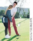 Man teaches young woman to play golf. Стоковое фото, фотограф Яков Филимонов / Фотобанк Лори