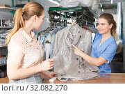 Купить «Worker returning clothing after dry cleaning», фото № 32082270, снято 9 мая 2018 г. (c) Яков Филимонов / Фотобанк Лори
