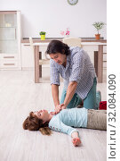 Купить «Young couple in first aid concept at home», фото № 32084090, снято 10 мая 2019 г. (c) Elnur / Фотобанк Лори