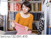 Купить «Woman looking for cloth in shop», фото № 32091410, снято 7 февраля 2019 г. (c) Яков Филимонов / Фотобанк Лори